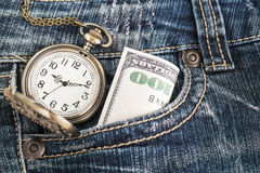 Pocket watch and a dollar bill in blue jeans Stock Photography