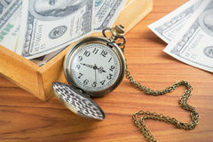 Pocket watch and dollar bills in wooden box Stock Photography