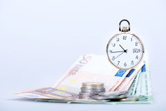 Pocket watch with euro banknotes and coins Royalty Free Stock Photos