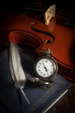 Pocket watch with feather on book and violin. Stock Photography