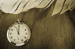Pocket Watch and Feather on Wood. Vintage Pocket Watch and Feather on Wood Stock Photography
