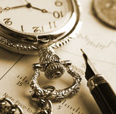 Pocket watch and fountain pen. Sepia view of retro pocket watch and fountain pen Stock Images