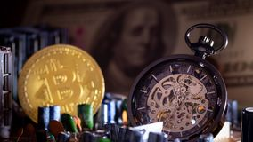 Pocket watch and gold bitcoin with dollar banknote on computer mainboard.