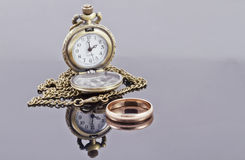 Pocket watch and a gold wedding ring Stock Photos