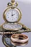 Pocket watch and a gold wedding ring Royalty Free Stock Image