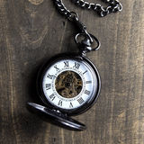 Pocket watch on grunge wooden table Stock Photos