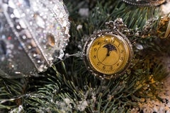 Pocket Watch Hanging on Decorated Evergreen. Close Up of Old Fashioned Pocket Watch Hanging on Snow Covered Sprigs of Evergreen Tree Decorated with Sparkling Royalty Free Stock Photo