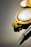 Pocket watch and ink pen on black Stock Photography