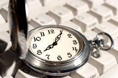 Pocket watch on the keyboard. Ancient pocket watch on the computer keyboard Royalty Free Stock Images