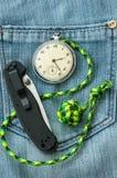 Pocket watch, knife on jeans Stock Photography