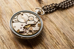 Pocket watch mechanism on wood background Stock Images