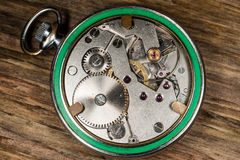 Pocket watch mechanism wood background Stock Image