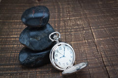 Pocket watch near the stones for spa. Stock Photos
