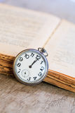 Pocket watch next to book Stock Image