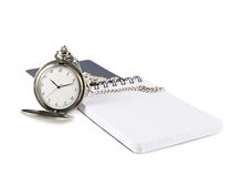 Pocket watch next to a note book Royalty Free Stock Photo