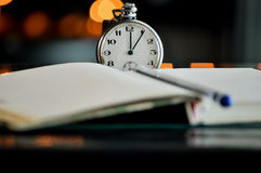 Pocket watch next to notebook. symbols of time Stock Image