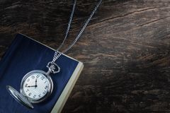 Pocket watch on an old book, a notebook. Stock Photo