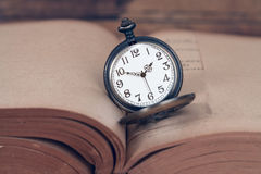 Pocket watch on old books. Stock Image