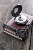 Pocket watch and old key on  wooden table Stock Image