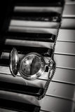 Pocket watch on old keyboard piano Stock Photos