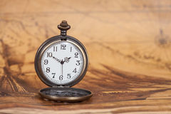 Pocket watch on old map background, vintage style. Light and tone Stock Photography