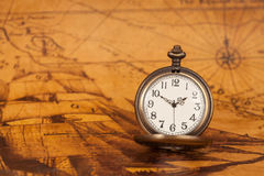 Pocket watch on old map background, vintage style. Light and tone Royalty Free Stock Photo