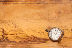 Pocket watch on old map background, vintage style. Light and tone Stock Photo