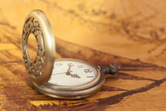 Pocket watch on old map background, vintage style. Light and tone Stock Photos