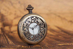 Pocket watch on old map background, vintage. Style light and tone Stock Images