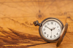 Pocket watch on old map background, vintage style. Light and tone Stock Images