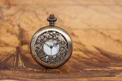 Pocket watch on old map background, vintage style. Light and tone Royalty Free Stock Photos