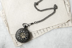 Pocket watch on old paper background Stock Images