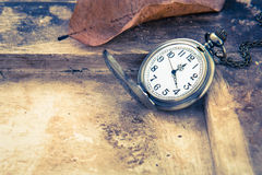 Pocket watch on old wooden background, vintage style. Light Royalty Free Stock Photo