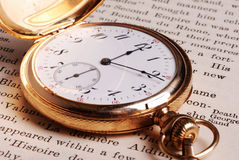 Pocket Watch on Open Book. Close-up view of an old pocket watch on the open pages of a book Royalty Free Stock Photography