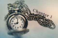Pocket Watch on the open Book with Blank Space in Vintage Tone Stock Photos