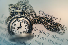 Pocket Watch on the open Book in Vintage Tone Stock Image