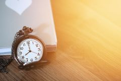 Pocket watch over the book on wooden table with light flare and copy space Stock Photo