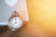 Pocket watch over the book on wooden table with light flare and copy space Stock Photos