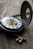 Pocket watch over grunge wooden table Stock Photos