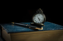 Pocket watch and pen on antique book. Royalty Free Stock Images