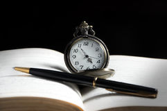 Pocket watch and pen on book. Royalty Free Stock Photo