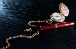 Pocket watch and pen Royalty Free Stock Photos