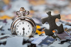 Pocket watch on a pile of jigsaw puzzle pieces Royalty Free Stock Photos