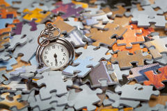 Pocket watch on a pile of jigsaw puzzle pieces Royalty Free Stock Photography