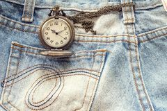 Pocket watch in pocket of jeans. Stock Image