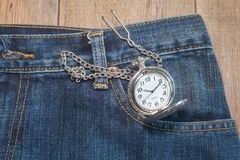 Pocket watch in pocket of jeans Stock Image