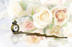 Pocket watch with rose bouquet on pastel tone background Stock Photos