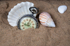 Pocket watch in the sand with seashells Stock Images