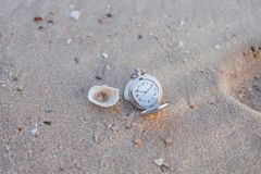 Pocket watch on sea beach. Background Stock Photo
