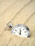Pocket watch semi buried in the sand Royalty Free Stock Photo
